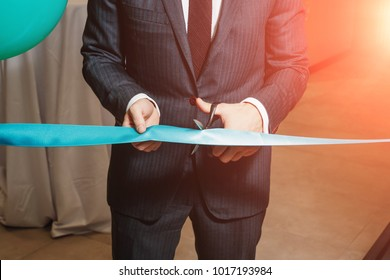 A man cutting a red ribbon, opening ceremony, isolated on white background