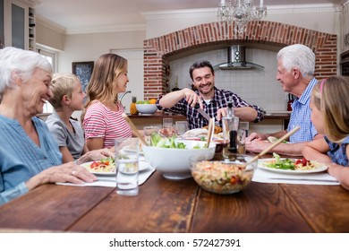 Man cutting roasted turkey while having meal with his family at home