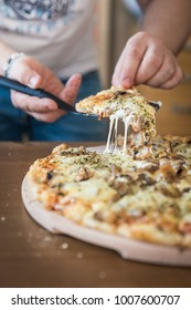 Man cutting slices of authentic homemade cheese pizza on wooden table