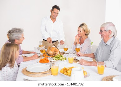 Man cutting slices of turkey for family dinner