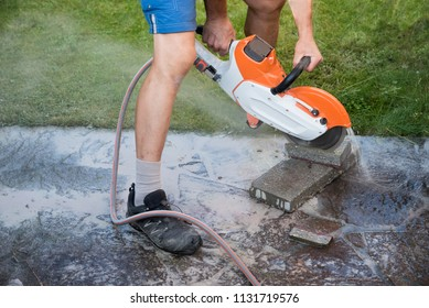 man cutting stone tiles with a circular saw. masonry saw with water supply