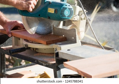 Man cutting wood with a saw outside in the sun during home renovations in the afternoon
