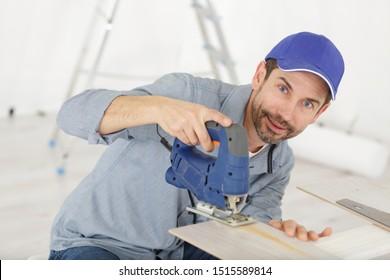 man cutting woodplank using bandsaw