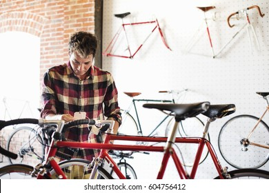 A man in a cycle shop, reading the price label on a bike
