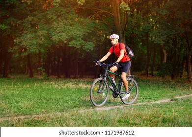Man cycling in the forest in the early autumn