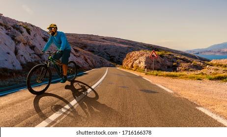 Man radelt auf dem Elektrorad, fährt bergwärts. Mann, der auf dem Fahrrad in kroatischer Landschaft fährt. Sportliche Aktivitäten im Freien.
