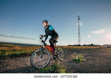 Man Cyclist with bike on sunrise at sunny summer