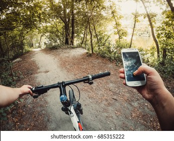 A man cyclist stands in the forest on a dirt road with a bicycle and holds a telphone in his hand. Copy space.