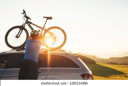 Man cyclist veared in cycling clothes and protective helmet instals his mountain bike on the car roof