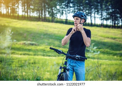 Man cyclist is wearing a sports gray helmet on his head in the background of green nature. The concept of mandatory protection during Cycling
