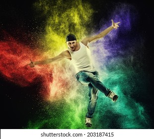 Man dancer showing break-dancing moves against colourful powder explosion