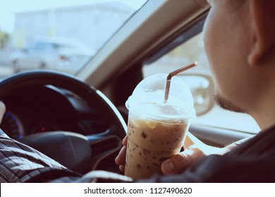 Man is dangerously drinking cup of cold coffee while driving a car