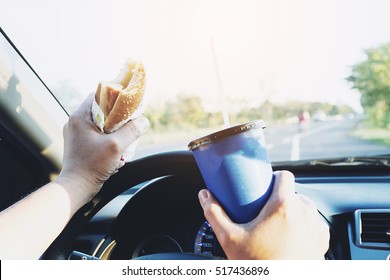Man is dangerously eating hot dog and cold drink while driving a car