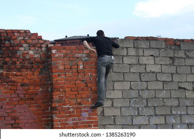 a man in dark clothes climbed onto an old brick fence and peeks over the wall