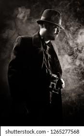 man in dark coat and hat on dark background