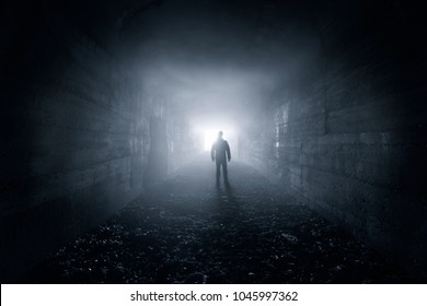 man in a dark concrete tunnel look out the exit - loneliness concept