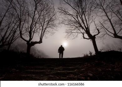 man in a dark forest with fog