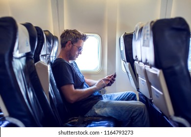 Man with dark hair is reading text message on mobile phone and speaking by phone during flying in the airplane