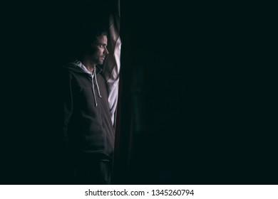 Man in the dark looking through a window