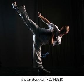 Man in dark practice martial art - high kick
