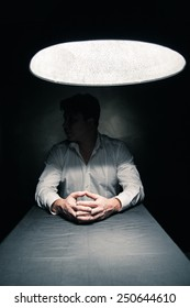Man in a dark room illuminated only by a light coming from a lamp no face seen