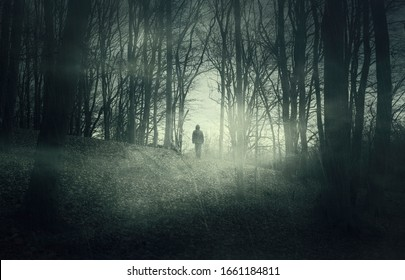 man in dark scary forest at night