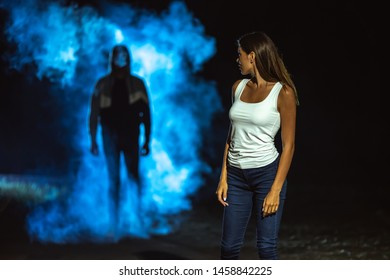 The man in the dark street following the woman