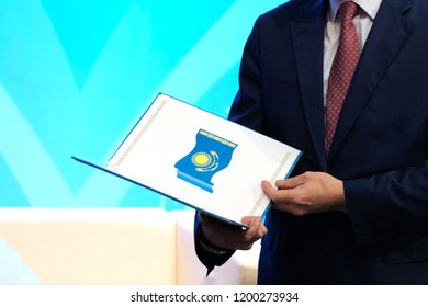 A man in a dark suit holds a opened folder with the image of the national flag of the Republic of Kazakhstan. The concept of awarding a civil servant. Blue background. Copy space.