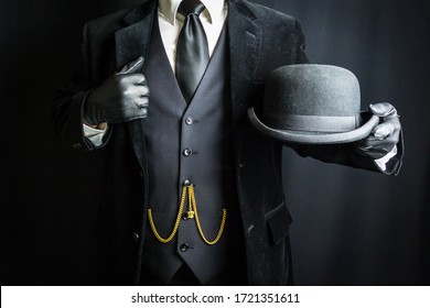 Man in Dark Suit and Leather Gloves Holding Bowler Hat on Black Background. Concept of Classic and Eccentric British Gentleman Stereotype. Retro Style and Vintage Fashion.
