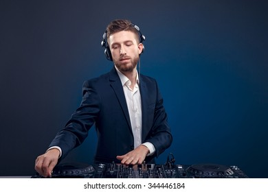 Man in dark suit play music on a DJ's mixer. Studio shot.