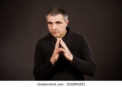 A man in a dark sweater on a black background. Emotional man himself upset, he pondered and made an important decision.