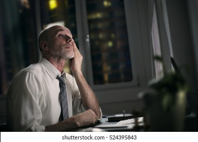 Man daydreaming while doing overtime