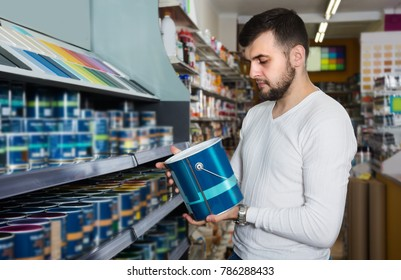 Man is deciding on best wall paint in paint supplies store.