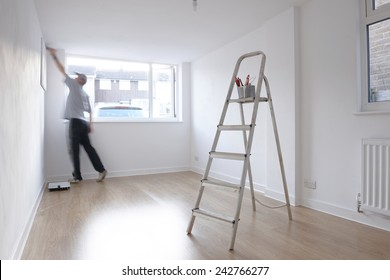 man decorating a room with ladder and paint pot in foreground