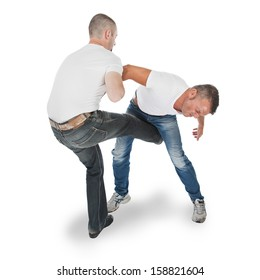 Man defending an attack from another man, selfdefense, kicking in groin, isolated on white