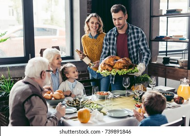 man with delicious turkey for holiday dinner with beautiful family