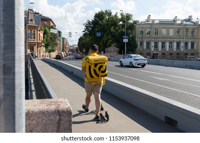 A man from the delivery service of food - Yandex, on the streets of St. Petersburg. Russia, St. Petersburg, Khrapovitsky Bridge, embankment of the Novo-Admiralteiskogo canal, August 4, 2018. EDITORIAL