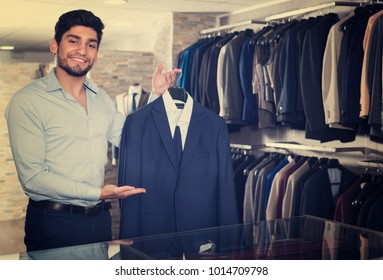 Man is demonstrating his choice of suit in clothes store