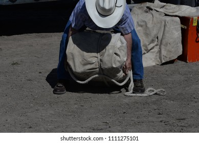 Man demonstrating how to tie a pack to put on a pack animal.