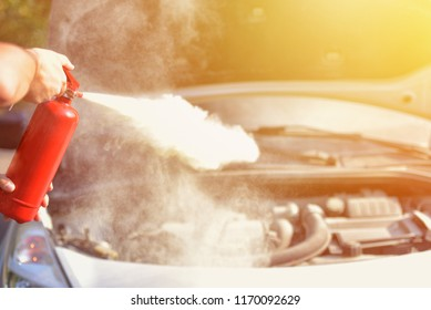 A man demonstrating how to use a fire extinguisher over a car engine