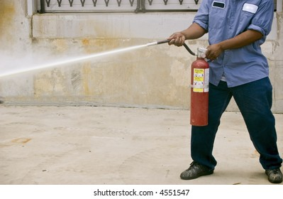 A man demonstrating how to use a fire extinguisher during a fire safety practice session.