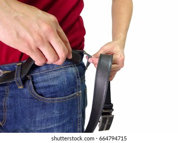 Man is demonstrating an inserting black belt into a loop of jean pant on waist level.