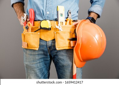 Man in denim clothes is standing with set of tools and holding hard hat in hand. Isolated on grey background