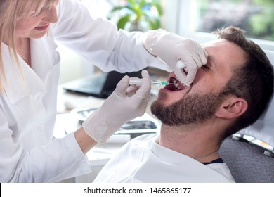 Man at the dentist. Injection with anesthesia performed by a pretty lady doctor.