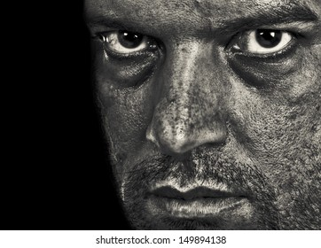A man depressed showing emotion and evil in the intense eyes. In Black and White.