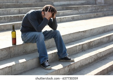 Man depressed with wine bottle sitting on stairs outdoor. People abuse and alcoholism problems.