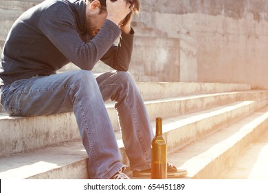 Man depressed with wine bottle sitting on stairs outdoor. People abuse and alcoholism problems. Toned photo.