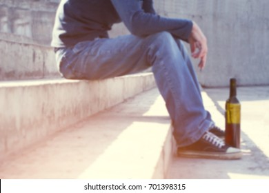 Man depressed with wine bottle sitting on stairs outdoor. People abuse and alcoholism problems. Out of focus