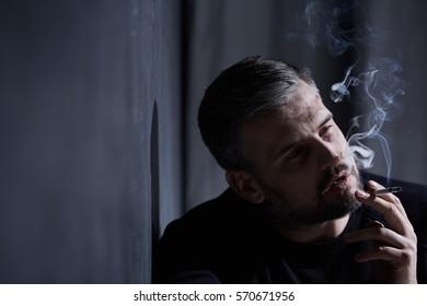 Man with depression inhaling cigarette smoke