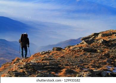 Man descending a mountain trail in autumn